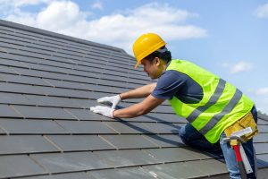 roof repair worker with white gloves replacing gray tiles shingles house with blue 1