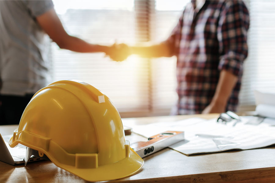 Business-Insurance-Two-Men-Shaking-Hands-Behind-a-Yellow-Hardhat.jpg